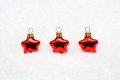 Christmas decoration. Three red Christmas decoration stars on a snowy background Stock Photo