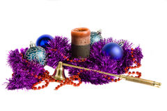 Christmas decoration. Blue christmas balls, candle, violet tinsel and candle snuffer, isolated royalty free stock image