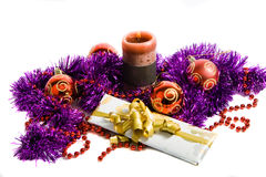 Christmas decoration. Red christmas balls, candle, gift box and violet tinsel royalty free stock photos