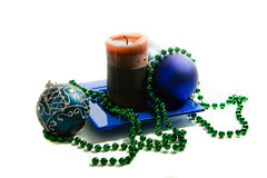 Christmas decoration. Blue Christmas balls, candle, green beads, isolated stock images