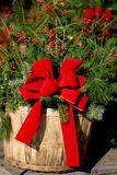 Christmas decoration. A basket with pine branches and bright red ribbon stock photo