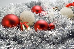 Christmas decoration. Red and silver globes on tinsel background with snowflakes pine cones christmas decorations Royalty Free Stock Image