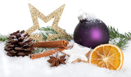 Christmas Decoration. Christmas Cookies, a bauble, some spices and a pine tree with a fire cone in snow stock image