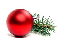 Christmas decoration. Single red Christmas bauble and tree branch decoration on a white background Stock Photography