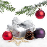 Christmas Decoration. A present, a branch, some baubles and a lot of snow on a white backgorund Royalty Free Stock Images