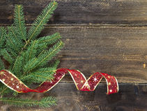Christmas decoration. Christmas fir tree with ribbon on wooden background Stock Images
