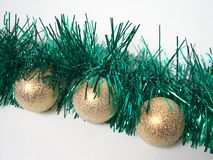 Christmas decoration. Two gold balls on a green tinsel Stock Photos