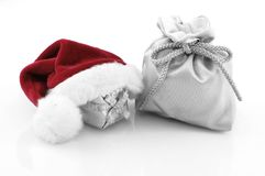 Christmas decoration. Silver gift bag with gift and red santa claus hat Royalty Free Stock Photography
