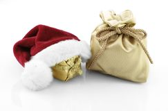 Christmas decoration. Golden gift bag with gift and red santa claus hat Stock Image