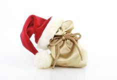 Christmas decoration. Golden gift bag with red santa claus hat Royalty Free Stock Photos