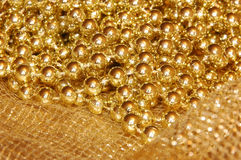 Christmas decoration. Golden holiday netting fabric and golden beads; could be used in backgrounds Royalty Free Stock Images