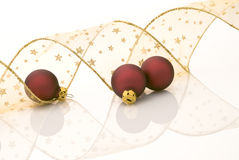 Christmas decoration. Satin red balls and golden ribbon decorated with stars on white background royalty free stock photography