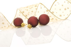 Christmas decoration. Satin red balls and golden ribbon decorated with stars reflected on white background royalty free stock images