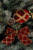 Christmas decoration. Of christmas red and gold ball, christmas red ribbon with gold stripes, on a christmas tree stock photos