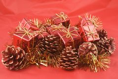 Christmas decoration. Background with little red parcels, balls and pines Stock Photography