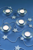 Christmas decoration. Candle lights and silver stars on blue background royalty free stock image