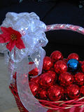 Christmas Decoration. Closeup of a red basket with lots of xmas balls, all of them are red except one, which is blue. The basket has a bow with a poinsettia as royalty free stock images