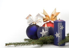 Christmas decoration. Christmas blue and red baubles with ornamental ribbon (bow) and burning candles arranged on Common Fir (Abies alba) twig Stock Images