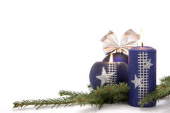Christmas decoration. Christmas blue bauble with ornamental ribbon (bow) and burning candles arranged on Common Fir (Abies alba) twig Royalty Free Stock Image