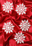 Christmas decoration. On red sateen with big flakes Stock Photos