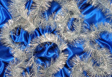 Christmas decoration. On blue sateen and tinsel Royalty Free Stock Images