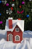 Christmas Decoration. Mini Red House covered by Heavy Snow with Christmas Tree Background Stock Photo