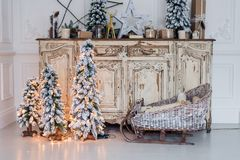 Christmas decoration on ancient vintage old commode chest of drawers. Hand made craft gifts, candels and a tree at Royalty Free Stock Photography