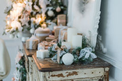 Christmas decoration on ancient vintage old commode chest of drawers. Hand made craft gifts, candels and a tree at background. Sel Royalty Free Stock Photos