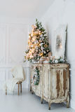 Christmas decoration on ancient vintage old commode chest of drawers. Hand made craft gifts, candels and a tree at background. Sel Royalty Free Stock Images