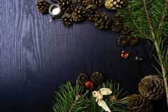 Christmas decoration, angel, cones, toys, teapot in black background and space for text. On a dark wooden background pine branches and decor, angel, cones, small stock photo