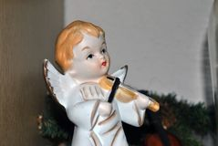 Christmas decoration of an angel doll with wings playing a violin stock photography