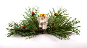Christmas decoration with angel figure and green branches. Ceramic decoration in the form of an angel with yellow hair, bright wings and robe, sitting in the Stock Photo