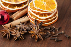 Christmas decoration. Anise stars, orange slices, cinamon, cloves and baubles in red Royalty Free Stock Image