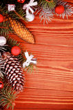 Christmas Decoration. Arrangement of Spruce Branch and Fir Cones with Hoarfrost, Red and Silver Baubles, Bows closeup on Wooden background Royalty Free Stock Image
