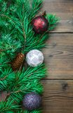 Christmas decoration background with branches and baubles. Christmas decoration backround with branches and baubles on the wooden background Royalty Free Stock Photos