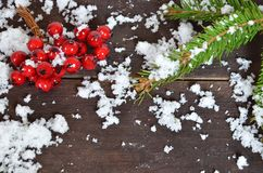 Christmas decoration background: fir branches, cones snow and holly red berries on brown wooden background stock photography