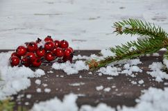 Christmas decoration background: fir branches, cones snow and holly red berries on brown wooden background stock photo