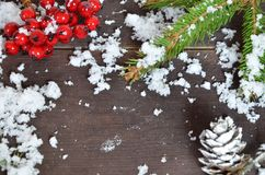 Christmas decoration background: fir branches, cones snow and holly red berries on brown wooden background stock image