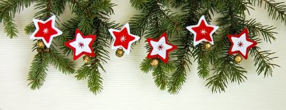 Christmas decoration background with red and wight felt stars and snowflakes with golden bells near fresh natural branches of Chri stock photography