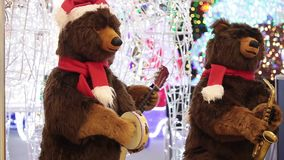 Christmas decoration background in shopping mall with two toy bears. Two toy bears in Santa Claus hats playing musical instruments and sing christmas songs in stock footage