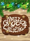 Christmas decoration on the background of the wooden planks. Christmas tree branch,. Bright multi-colored lights on a bright wooden background. Poster for the Stock Image
