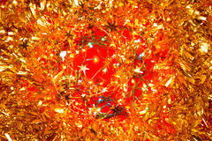 Christmas decoration background. Christmas decoration with yellow tinsel on red background stock photos
