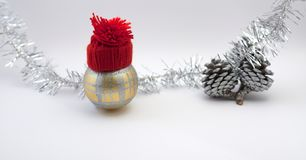 Christmas decoration ball with red handmade red hat. Christmas decoration ball and pine cones. Silver ribbon, soft white background Royalty Free Stock Photography