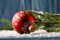 Christmas decoration ball on snowy tree on blue background Royalty Free Stock Images