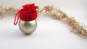 Christmas decoration balls with handmade red hat. Christmas decoration ball wihh red hat. Silver ribbon, soft white background Royalty Free Stock Image