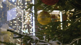 Christmas decoration balls hanging on tree on the background lights garland. Shiny yellow ball. Christmas decoration balls hanging on tree on the background stock video