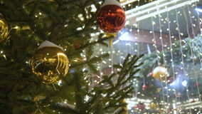 Christmas decoration balls hanging on tree on the background lights garland. Shiny yellow ball. Christmas decoration balls hanging on tree on the background stock footage