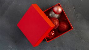 Christmas decoration balls in opened red gift box on black ckalk board backgroud with copy space. Top view. Horizontal