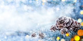 Christmas Decoration Banner. Snowy Pine Cones On Spruce Branch With Lights royalty free stock photo