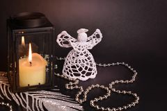 Christmas decoration on black background. White crochet angel, lantern, candle, silver feather and beads. Christmas decorations on black background. White royalty free stock photo